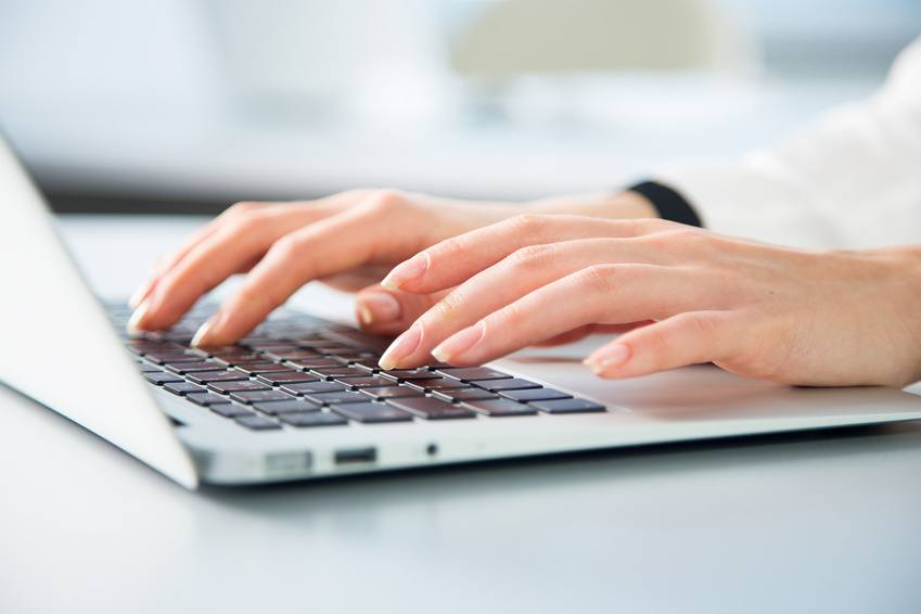 Closeup of businesswoman typing on laptop computer